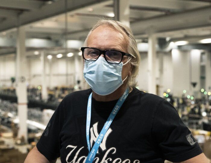 Primo piano di un uomo di mezza età. Indossa degli occhiali da vista neri, una t-shirt nera con delle stampe bianche e una mascherina chirurgica sul volto. Sullo sfondo si vede un magazzino Amazon.