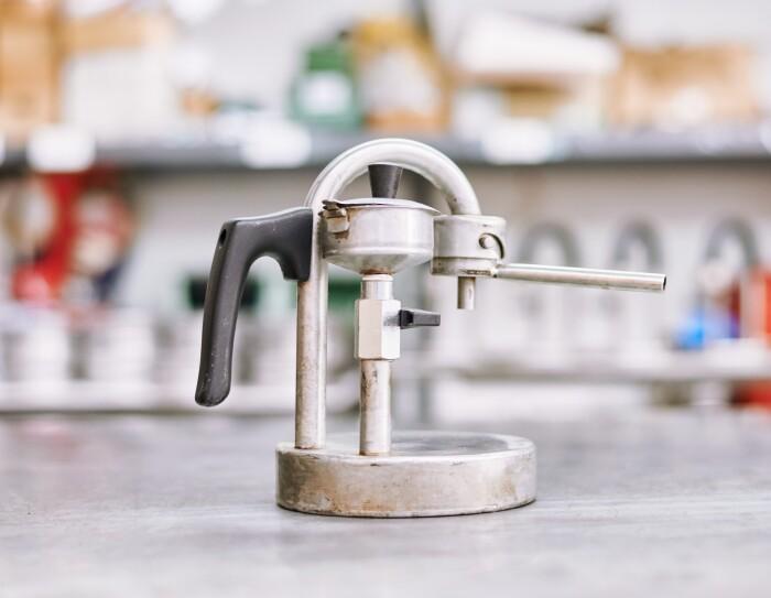 Foto di prototipo un po' bruciacchiato di caffettiera Kamira, con manico, collo a U invertita ed erogatore. Vista di lato.