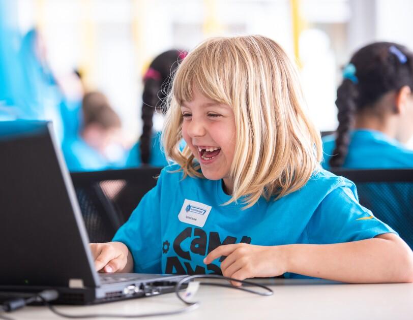 Ein blondes Mädchen im blauen Camp-Amazon-Shirt sitzt vor einem Laptop und lacht