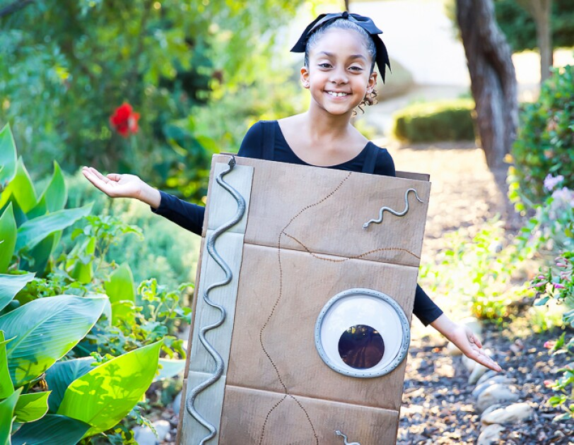 A young girl wears a costume made of an Amazon box, decorated to look like a spell book with a giant eye and silver snakes. The box is attached with shoulder straps and covers from her shoulders to her knees. The