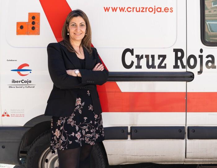Olga Díaz, subdirectora de Inclusión Social de Cruz Roja. Con un vestido negro estampado con flores rosas, unas medias negras y una americana también negra. el pelo castaño liso por el hombro y uos pendientes con una perla colgando y un reloj en la muñeca izquierda. Está con los brazos cruzados apoyada en una furgoneta de Cruz  Roja. La furgoneta es blanca y lleva escrito Cruz Roja.