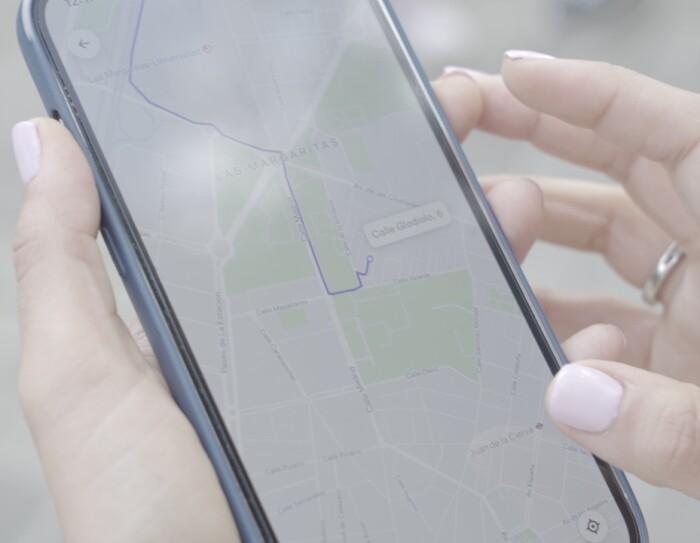 Cabify es la primera empresa europea de movilidad neutra en carbono. Dos manos con la manicura hecha y un anillo de boda en la mano izquierda. Con las dos manos sujeta un teléfono móvil qu een la pantalla tiene abierta la aplicación de Cabify con el recorrorido en color morado hasta llegar al destino deseado.