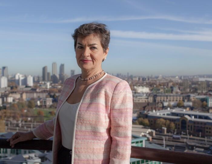 Christiana Figueres con el pelo corto y apoyada en una barandilla mira a cámara. De fondo se ve una ciudad Ella lleva unos pendientes y un collar de perlas, una chaqueta rosa y un jersey blanco.