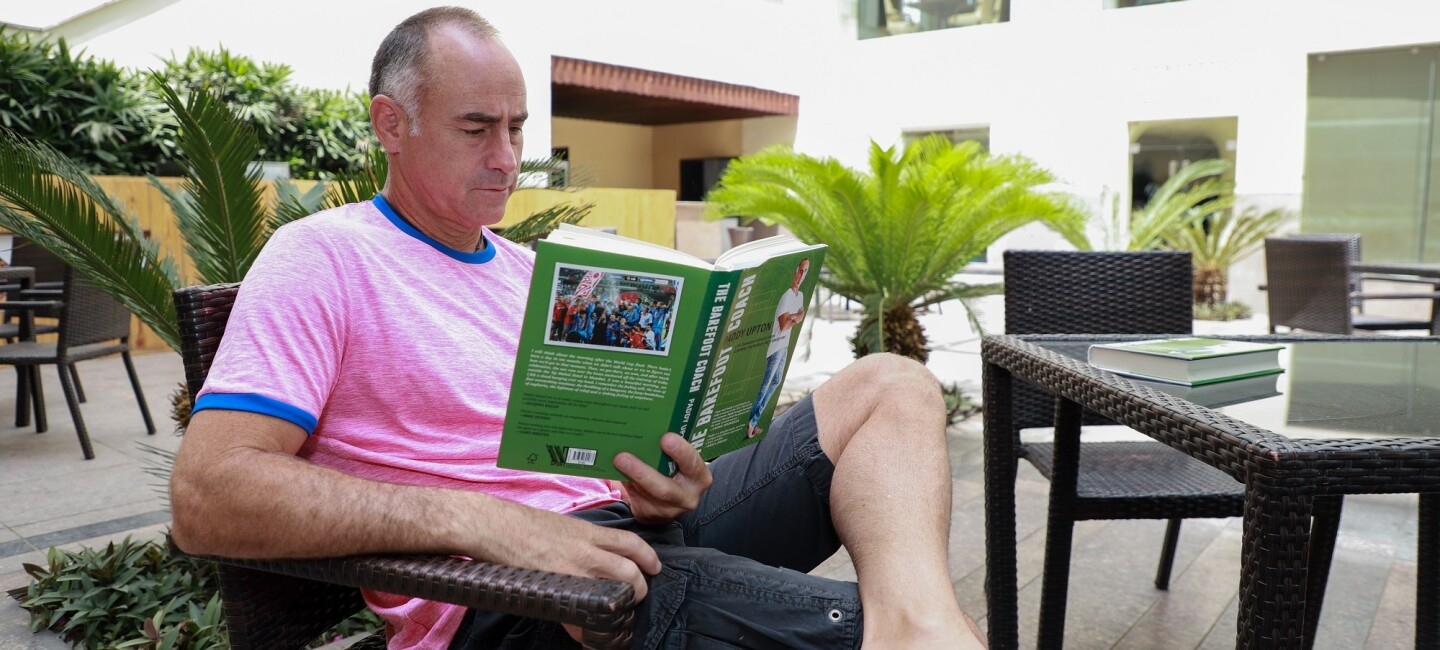 Paddy Upton on a chair  reading a book