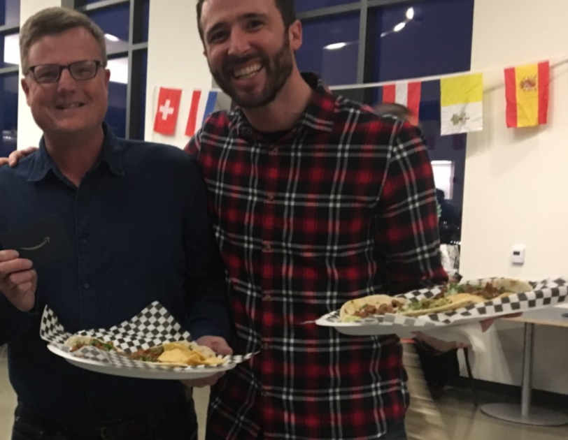 Two men smile for the camera while holding plates with tacos on them.
