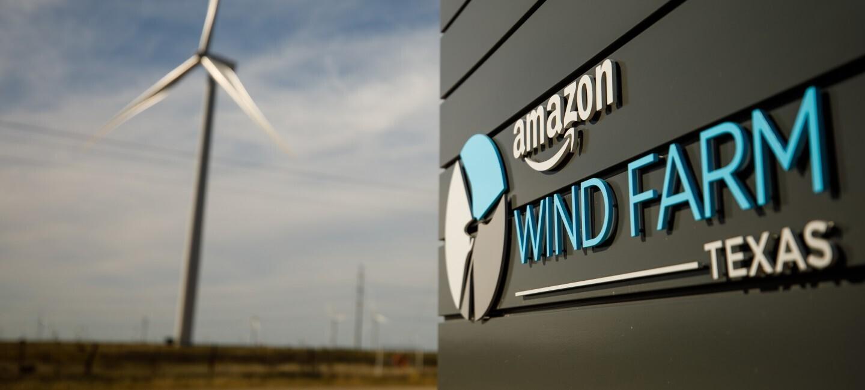 Logo Amazon oraz tekst 'Wind Farm Texas' na czarnej ścianie, w tle farma wiatrowa
