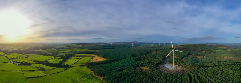 L'immagine mostra distese di campi verdi e boschi, da cui svettano alcune pale eoliche sullo sfondo