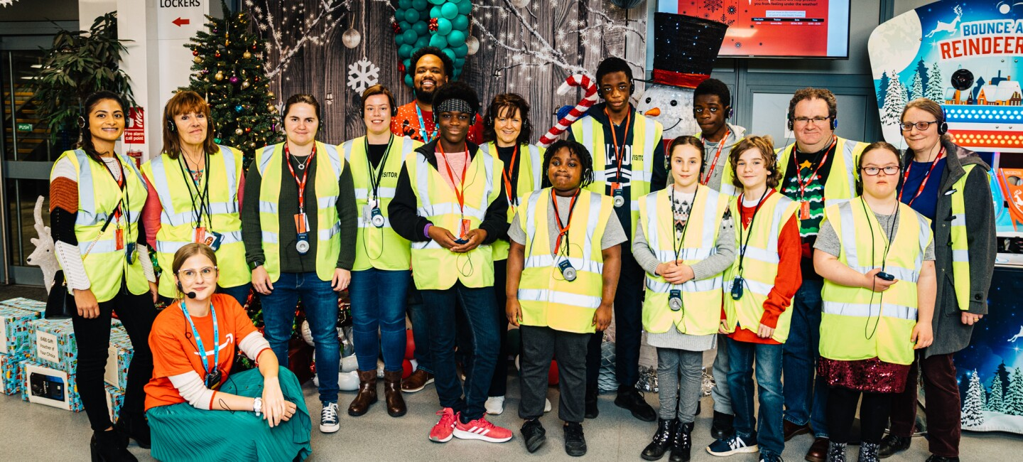 Group shot of children and supervisors at the Barnardo's tour of Amazon's Dunstable Fulfilment Centre. There are lots of Christmas decorations around them.