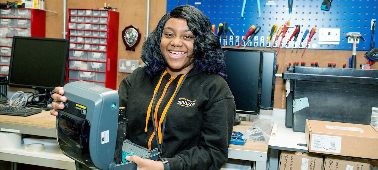 Apprentice, Shannia Daley, pictured in the workshop in an Amazon fulfilment centre holding an open printer machine and smiling.