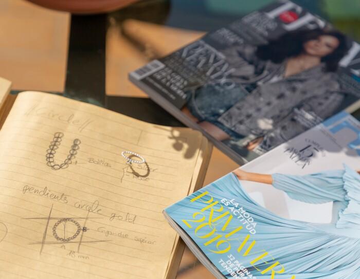 SOnia Llamas de Iyé Biyé está preparando una nueva colección. En la foto hay dos revistas de moda y una libreta con sus diseños dibujados. Al lado de uno de sus diseños, la joyas hecha realidad.