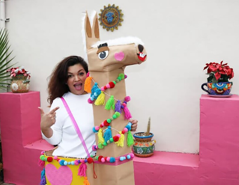 "A woman in her ""llama boxtume"" - a costume made of Amazon boxes, with a larger box as the llama body, a tall box for the neck, and a smaller box for the head, the llama has felt details for eyes, nose and mouse, and is wrapped in decorations made of pom poms and tassels."