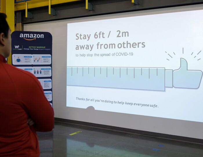 Les pancartes et écrans dans les centres de distribution d'Amazon rappellent aux collaborateurs de respecter une distance de 2 mètres.