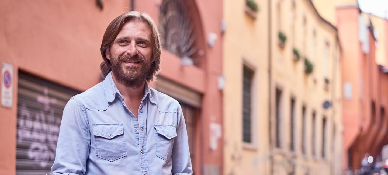 L'imprenditore Massimo Ciociola, fondatore e CEO di Musixmatch, sullo sfondo di una via bolognese