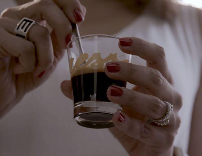Primo piano di due mani femminili che reggono una tazzina di caffè in vetro. Sulla tazzina si intravede il logo 'Yespresso'. La donna, di cui non si vede il volto, indossa una canotta bianca, ha due anelli su entrambi gli anulari e lo smalto rosso. La sua mano sinistra regge la tazzina, mentre con la destra gira il caffè con un cucchiaino.