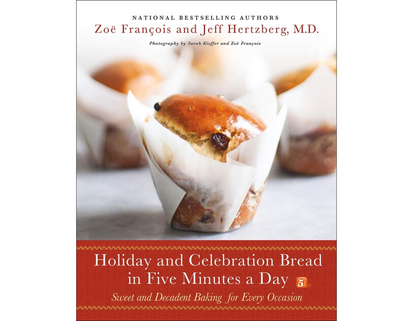 A holiday cook book with a celebration bread in parchment paper wrap, in front of other bakery treats.