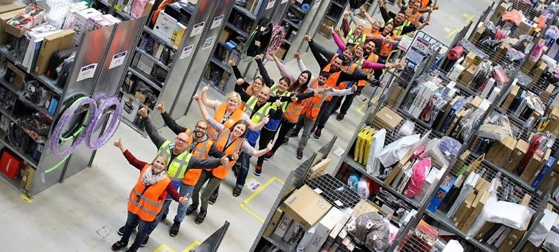 Eine Reihe von Logistikmitarbeitern stehen nacheinander im einem Regalgang, die Daumen nach oben
