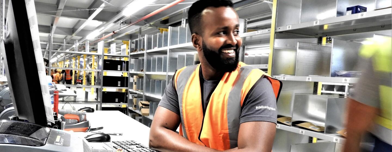 Ein Mitarbeiter in orangener Sicherheitsweste vor einem PC, im Hintergrund sieht man Regalfächer.