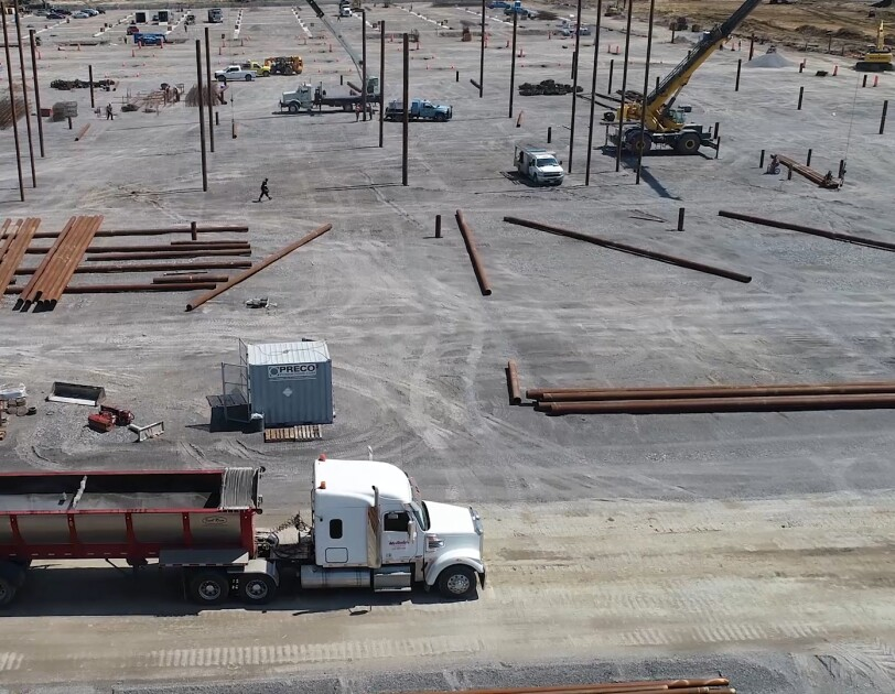 Aerial view of a semi-truck driving into a construction site.