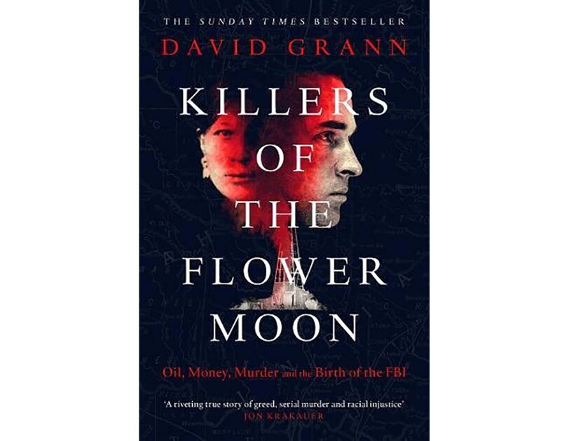 "Book cover for ""Killers of the Flower Moon"" - a woman's face on the left, a man's profile on the right. Both faces have a red tone of them. The background is black, and title text is white."