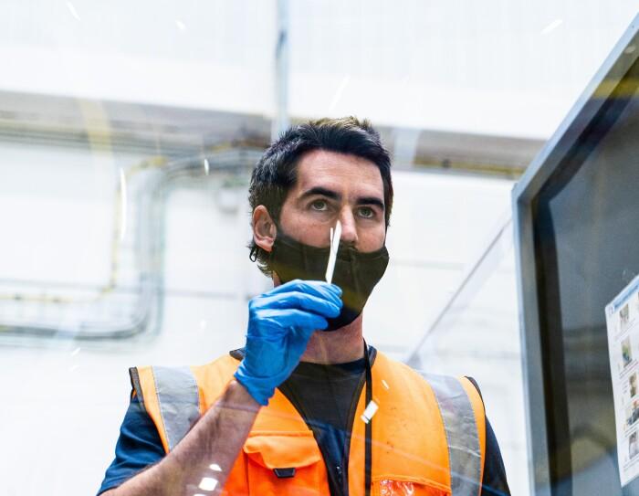 Nacho Carbonell realizándose una PCR en el centro logístco de El Prat de Llobregat. Con una mascarilla negra debajo de la nariz y un guante azul en la mano derecha, sacándose una muestra de la nariz. El plano llega hasta el pecho. Va con una camiseta negra de manga corta y un chaleco naranja. En la parte izquierda una mampara con las instrucciones para realizarse una PCR.