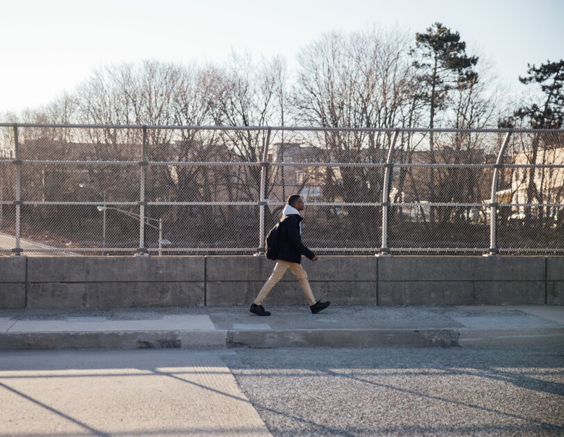 A teenage boy strides along a sidewalk. Chain-link fencing and what appears to be a roadway are behind him.