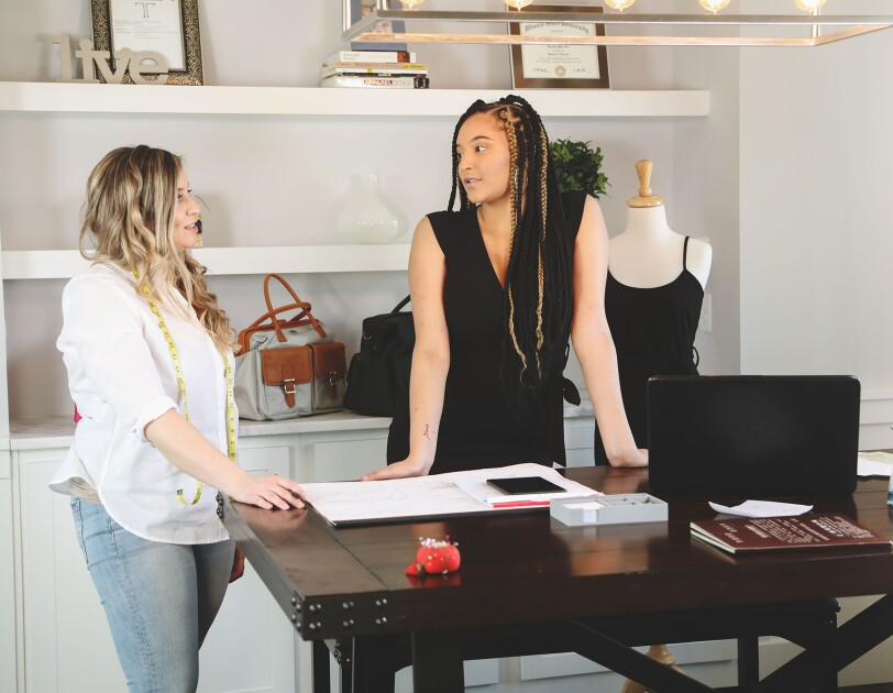 A blond woman wearing jeans and a white button up stands at a desk, engaged in conversation with a woman with long braids, wearing a little black dress.