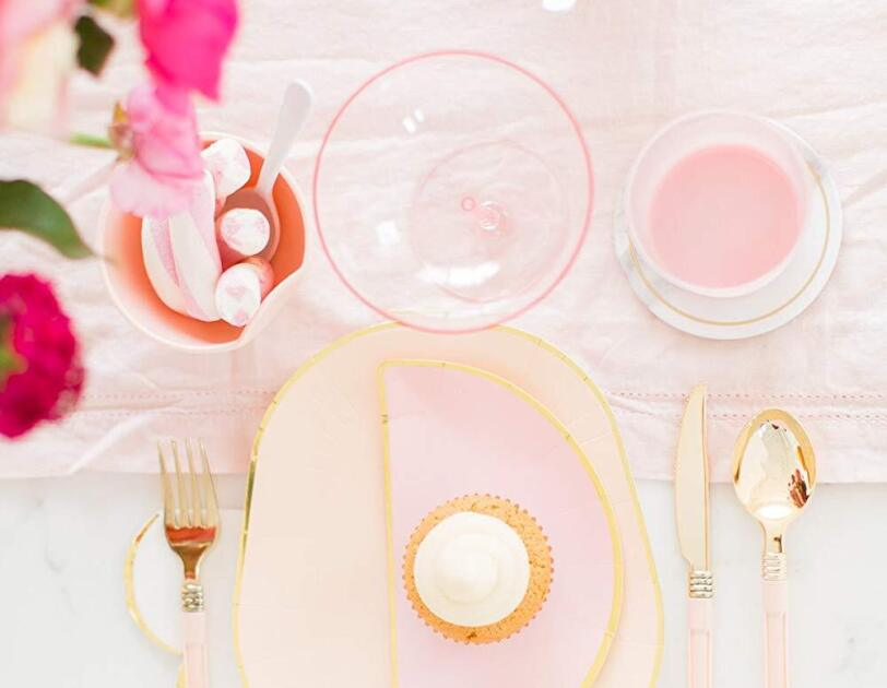 Pink champagne glasses sit atop a pink table runner on a marble table top. At each place setting, elegant dishes trimmed in gold and golden cutlery sit.