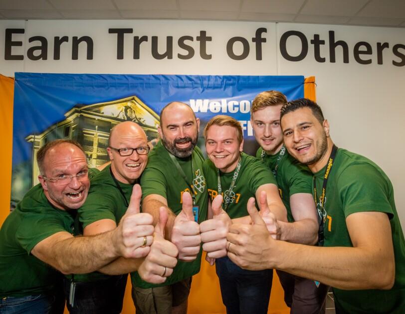 Sechs Mitarbeiter, männlich, alle mit grünen T-shirts und mit Daumen nach oben, stehen vor einem Willkommensplakat, das nicht vollständig sichtbar ist. Über dem Plakat eine Aufschrift: Earn trust for others. Alle Mitarbeiter lächeln.
