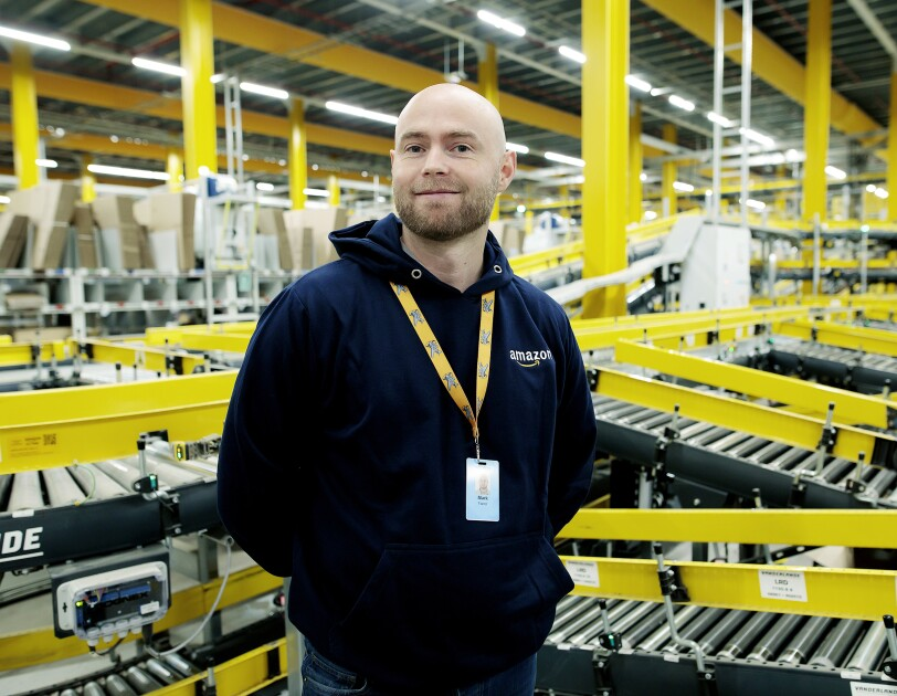Retired Royal Navy Officer, Mark Farrer pictured smiling in front of machinery at an Amazon fulfilment centre