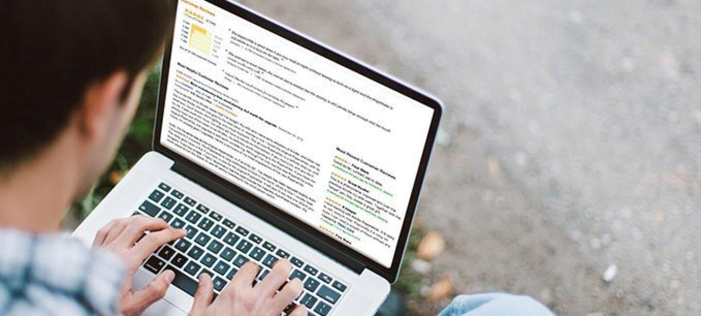 Un uomo, di spalle, scrive una recensione Amazon. Sullo schermo del PC compaiono tutte le altre recensioni del prodotto.