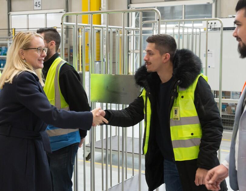 Die Wirtschaftsministerin und ein Mitarbeiter in gelber Sicherheitsweste schütteln sich die Hände. Im Hintergrund: weitere Mitarbeiter und Besucher.