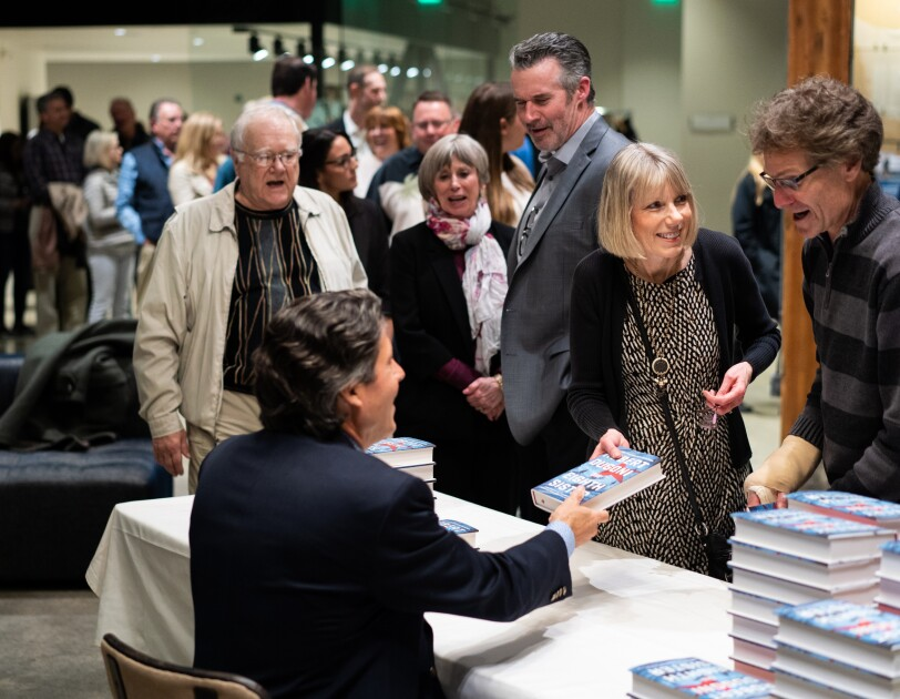 Author Robert Dugoni sits at a table at a book signing event. Fans stand near him, leaning in to get a book signed and share a few words.