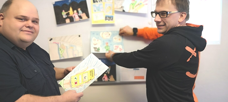 Zwei Männer in schwarzen Pullis stehen vor einer weißen Pinnwand, auf der sie die neue Juleica-App planen.
