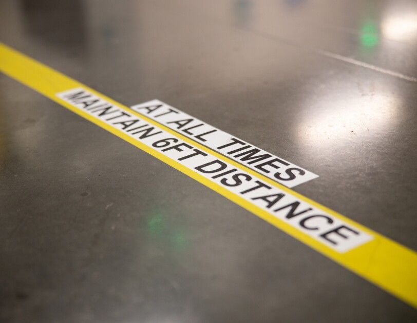 "Markings on a concrete floor in a workplace say ""MAINTAIN 6FT DISTANCE AT ALL TIMES."""