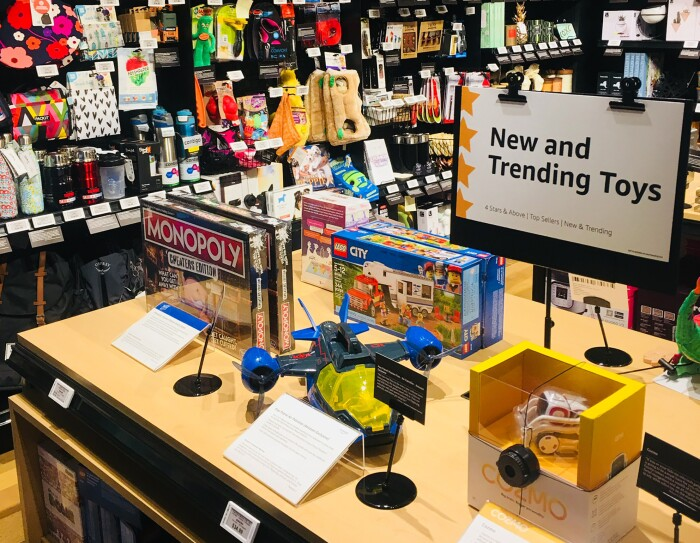 "A table of ""New and Trending Toys"" at the Amazon 4-star store. On the table are a Monopoly board game, LEGO City set, and COZMO robotic toy. Each product has a digital price tag and a customer review displayed alongside the item. Behind the table are Gifts for Pets, Gifts for Grown-Ups, and Candles & Home Decor."