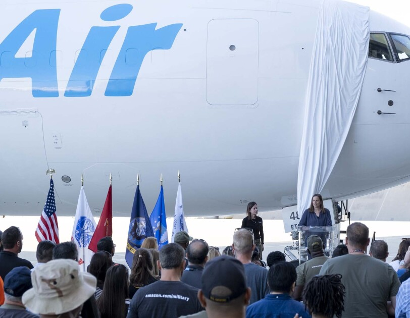 Ardine Williams and Sarah Rhoads stand in front of the newest Amazon Air plane, speaking to a crowd. The plane's official name is covered, soon to be unveiled by Jeff Bezos.