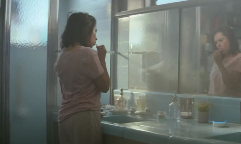 A dark-haired woman in a pink shirt and sweat pants brushes her teeth in a mirror while an Amazon Echo Dot rests on the counter. The counter is 1970s blue tile.