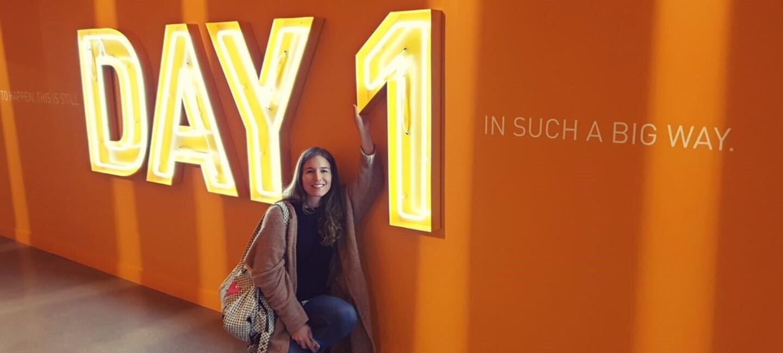 Eine Gewinnerin der Unternehmerinnen der Zukunft-Reise nach Seattle, sitzt vor einer orangenen Wand mit einer großen Leutschrift: Day 1