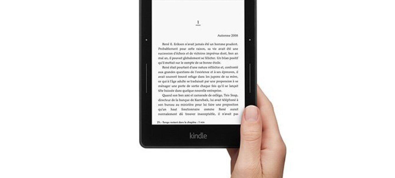 Une main de femme tient une lieuse Kindle sur laquelle s'affiche le premier chapitre d'un livre