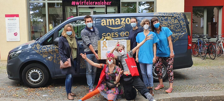 """Amazon Mitarbeiter:innen, Rote Nasen Clowns und Krankenhaus Mitarbeiter:innen vor dem mit """"Amazon goes gold"""" beschrifteten Liefervan"""