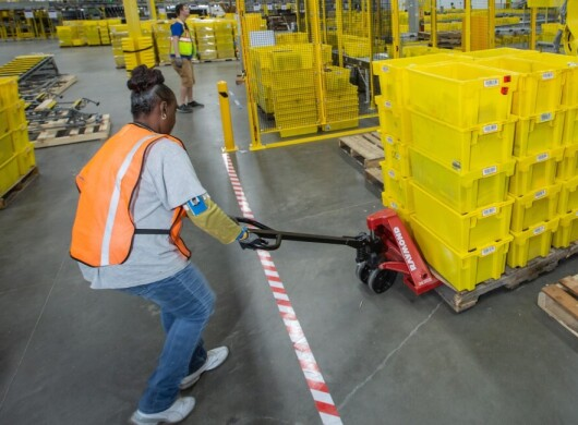 An Amazon employee pulls a pallet of packing crates with a hand truck in an Amazon Fulfillment center.
