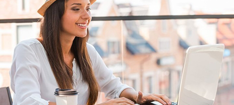 Mujer de mediana edad con un gorro, camisa blanca y un vaso de café, trabaja delante de un ordenador también blanco en la terraza de un edificio.
