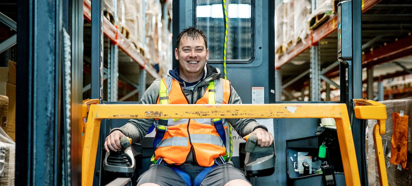 Apprentice, Nicholas Hart, pictured operating a forklift and smiling at the camera