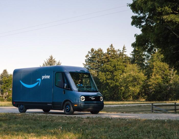 Furgone elettrico Rivian in una strada di campagna. Il furgone è blu e sulla fiancata ha il logo smile di Amazon e la scritta 'Prime'