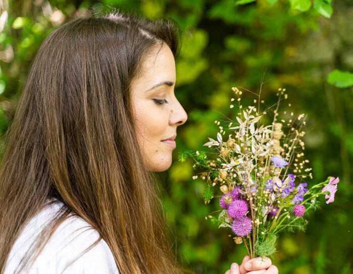 Alejandra Gómez Iribarnegaray oliendo plantas del bosque con los que también fabrican los jabones sólidos de La cosmética de María.