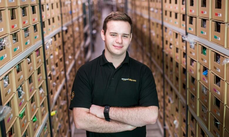 Amazon apprentice Jonathon Williams standing between shelves