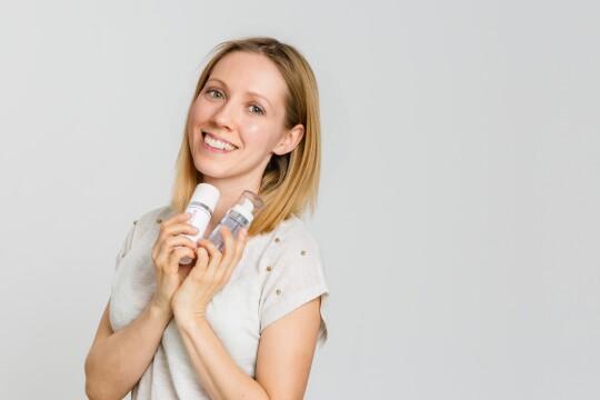 Eine blonde Frau mit Reinigungsprodukten in ihren Händen lächelt in die Kamera.