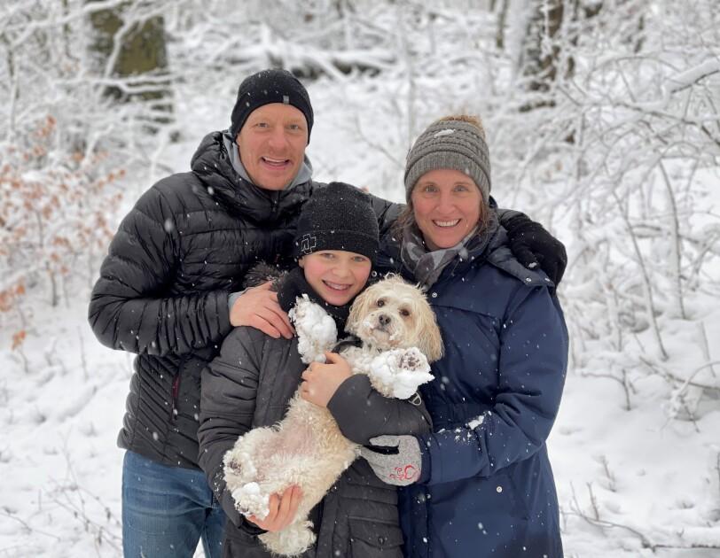 Ein Mann, eine Frau und ein Kind mit Hund in den Armen stehen im Schnee und lachen in die Kamera.