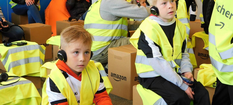 Zwei kleine Jungen in Sicherheitswesten sitzen auf Amazon Kartonhockern