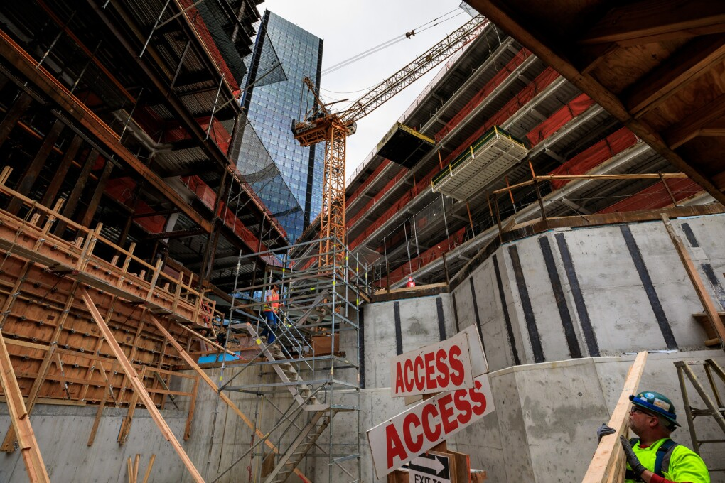 "Buildings under construction on Amazon's South Lake Union campus. A construction worker carries 2x4s next to an ""access"" sign. A temporary staircase is in place near a crane."